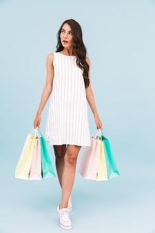 Belle jeune femme posant mur isolé tenant des sacs à provisions.