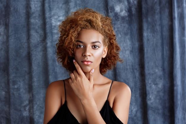 Belle jeune femme posant sur un mur de tissu gris