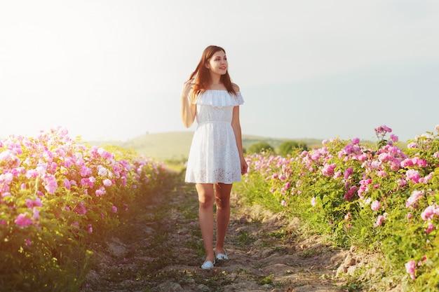 Belle jeune femme posant près de roses dans un jardin,