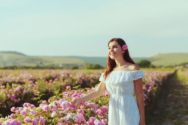 Belle jeune femme posant près de roses dans un jardin.
