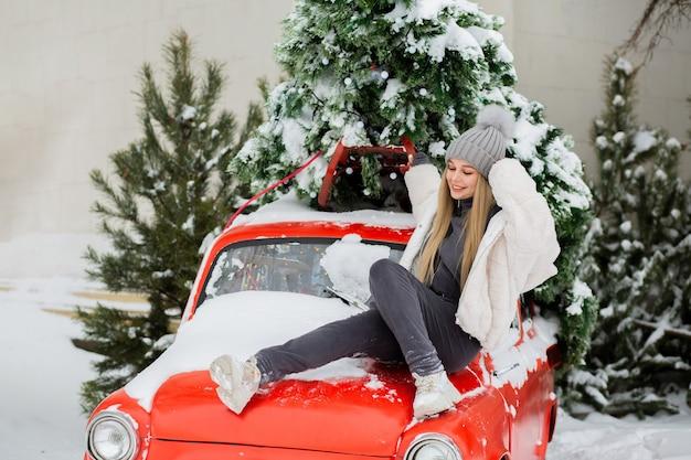 Belle jeune femme posant près d'une vieille voiture rouge