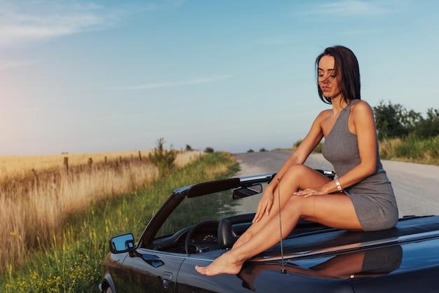 Belle jeune femme posant près d'une voiture sur la route