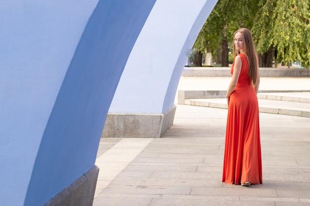 Belle jeune femme posant avec une robe rouge dans la rue