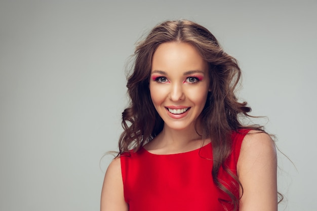 Belle jeune femme posant avec une robe rouge