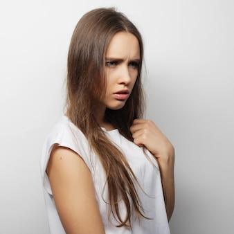 Belle jeune femme posant avec des t-shirts blancs, fond blanc ower