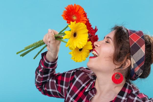 Belle jeune femme positive dans une chemise à carreaux et un bandage reniflant de belles fleurs de gerbera lumineux posant sur une surface bleue