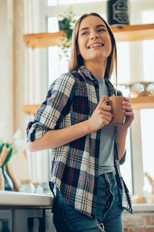 Belle jeune femme positive souriante à la maison avec une tasse dans les mains