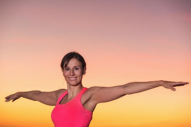Belle jeune femme pratiquant le yoga au coucher du soleil