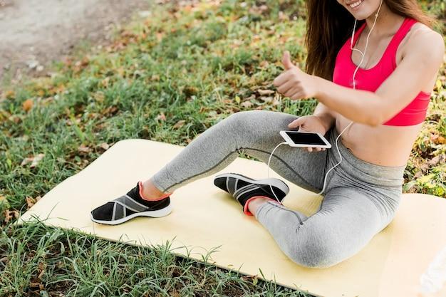 Belle jeune femme pratiquant le yoga dans le parc verdoyant.