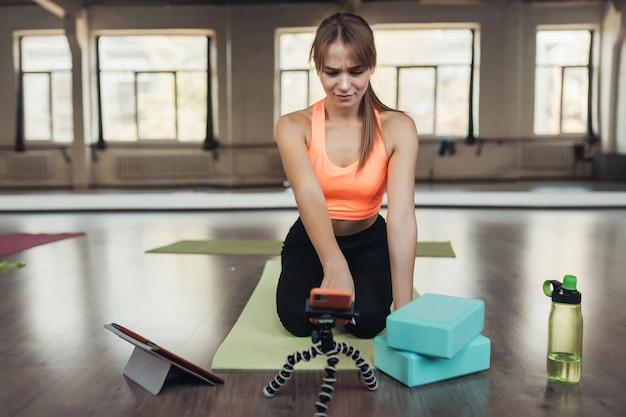 Belle jeune femme pratiquant le yoga, est engagée avec l'enseignant en ligne via une tablette. concept de sport à domicile.