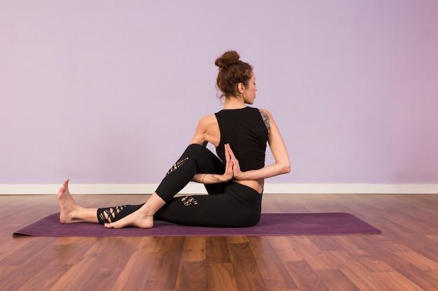 Belle jeune femme pratiquant le yoga à l'intérieur