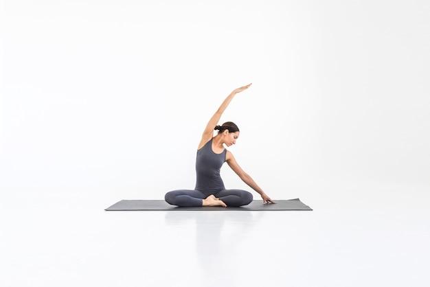 Belle jeune femme pratiquant le yoga sur le tapis faisant des étirements