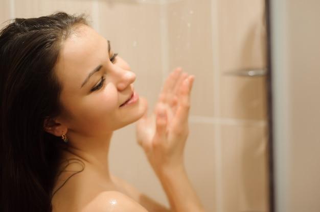 Belle jeune femme prenant une douche relaxante.