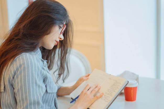 Belle jeune femme prenant des notes dans le bloc-notes, profitant du temps de loisirs dans un café élégant