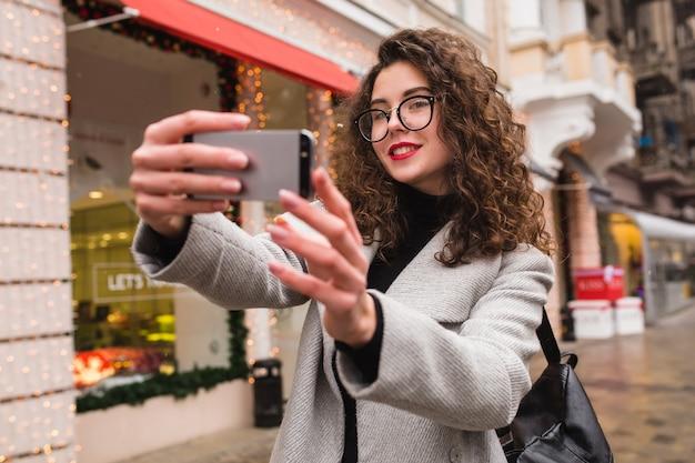 Belle jeune femme prenant une photo de seflie à l'aide de smartphone, style de ville de rue automne, manteau chaud, lunettes, heureux, souriant, tenant le téléphone à la main, cheveux bouclés