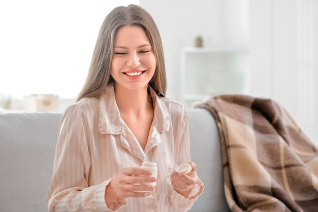 Belle jeune femme prenant des pilules à la maison