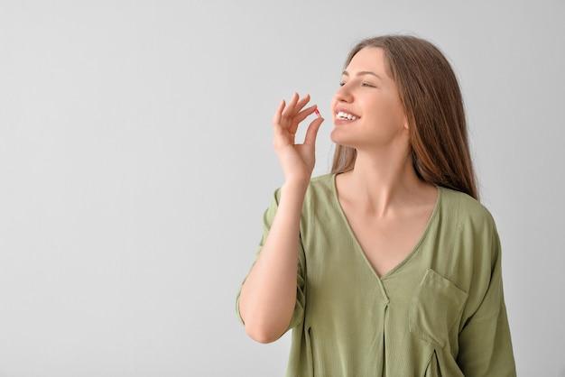 Belle jeune femme prenant des pilules sur une surface grise