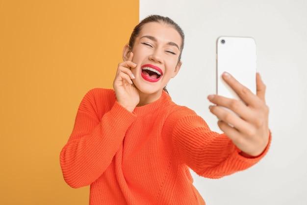 Belle jeune femme prenant selfie sur couleur