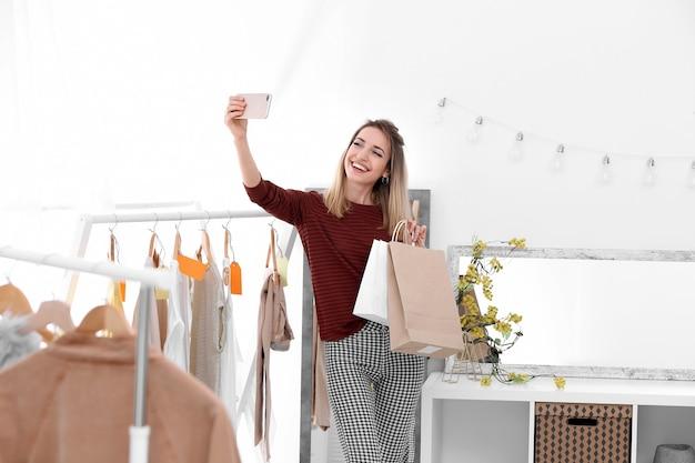 Belle jeune femme prenant selfie lors de vos achats en magasin