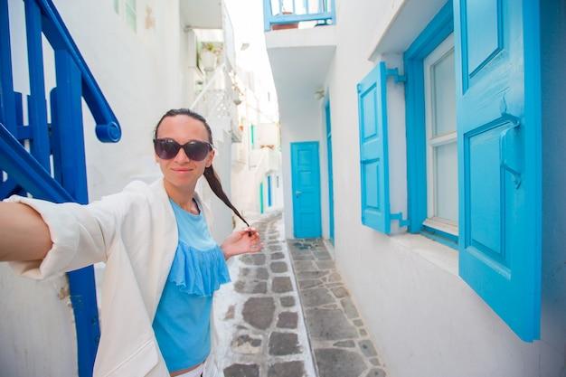 Belle jeune femme prenant selfie avec téléphone extérieur maison blanche fond extérieur