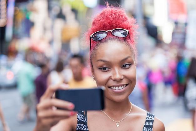 Belle jeune femme prenant selfie à times square