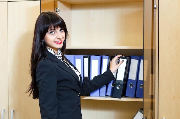 Belle jeune femme prend un dossier avec des documents du cabinet