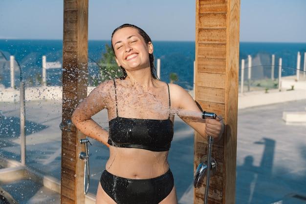 Belle jeune femme prend une douche relaxante en maillot de bain sur une journée ensoleillée à l'extérieur au bord de la mer.