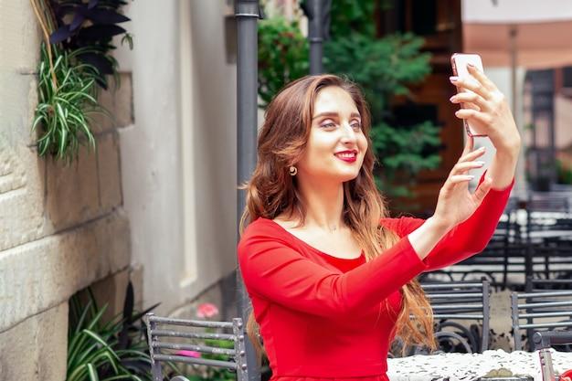 Belle jeune femme prend selfie par smartphone à la table du café, à l'extérieur.