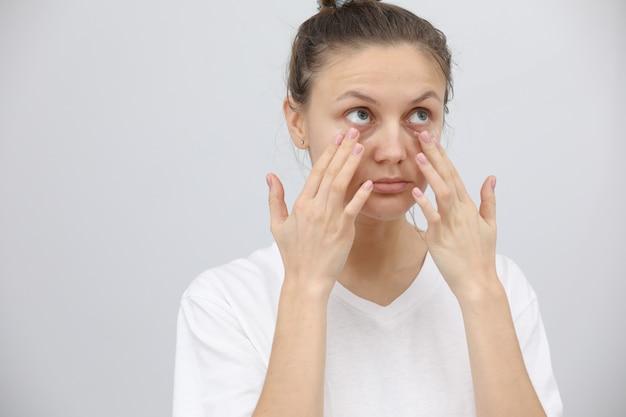 Belle jeune femme prend soin de la peau autour des yeux.