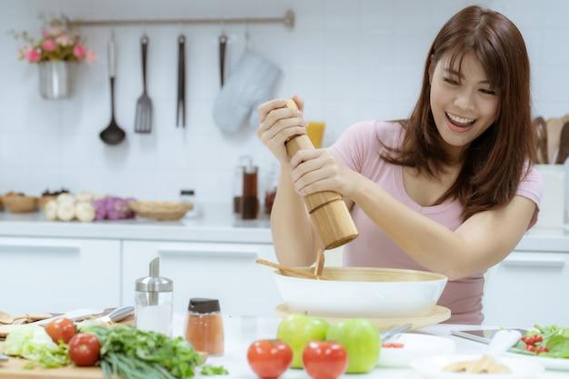 Une belle jeune femme prend soin de sa santé en mangeant de la salade et des fruits au lieu de manger de la graisse et des calories