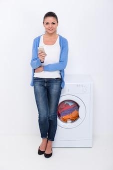 Belle jeune femme près de la machine à laver.