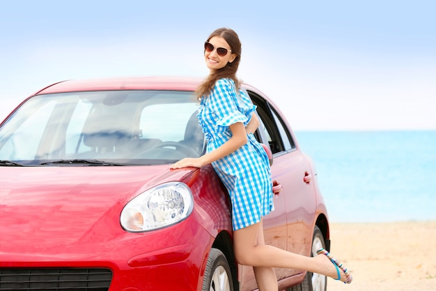 Belle jeune femme près de la voiture à la station balnéaire