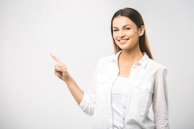Belle jeune femme présentant votre produit isolé