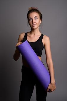 Belle jeune femme prête pour la gym contre le mur gris