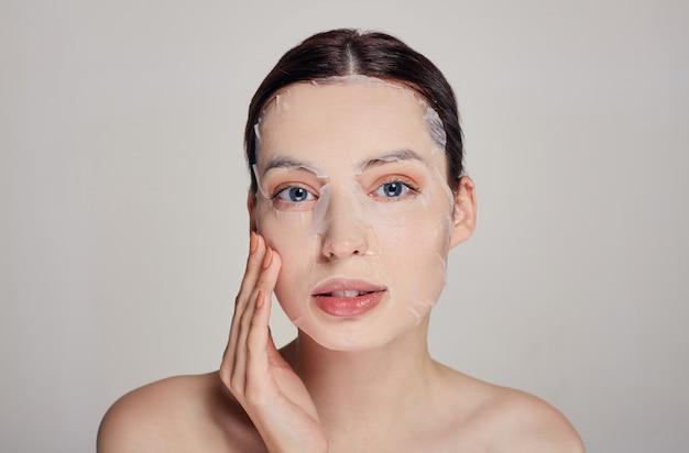 Belle jeune femme pritty aux yeux bleus et lèvres pleines avec masque hydratant, toucher son visage. gris. cheveux foncés. avoir hâte de. copiez l'espace.