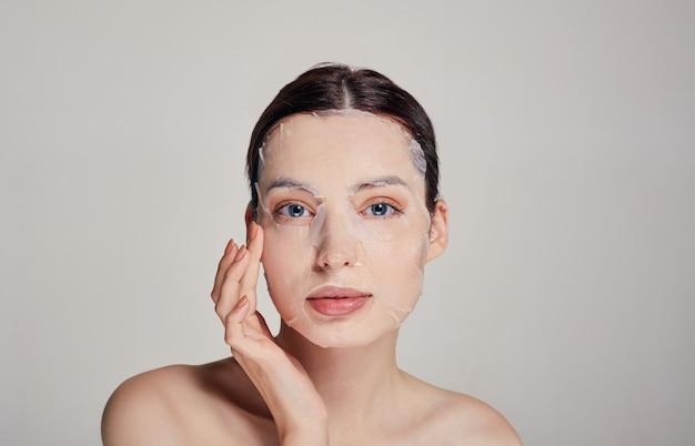Belle jeune femme pritty tendre aux yeux bleus et lèvres pleines avec masque hydratant, toucher le visage. cheveux foncés. en regardant droit. copiez l'espace. spa, cosmétologie.