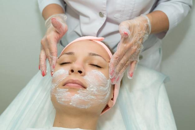 Belle jeune femme sur la procédure de nettoyage du visage en cosmétologie