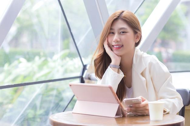 Belle jeune femme professionnelle asiatique dans un costume de couleur crème tient un smartphone pour discuter et enregistrer des informations à envoyer au bureau sur une tablette dans un café.