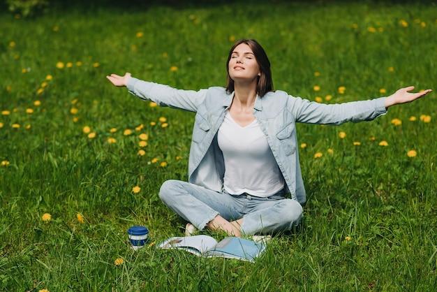 Belle jeune femme profiter de la nature assise dans le parc avec livre et café