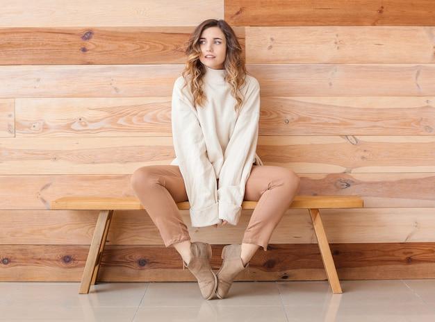 Belle jeune femme en pull chaud assis sur un banc près d'un mur en bois