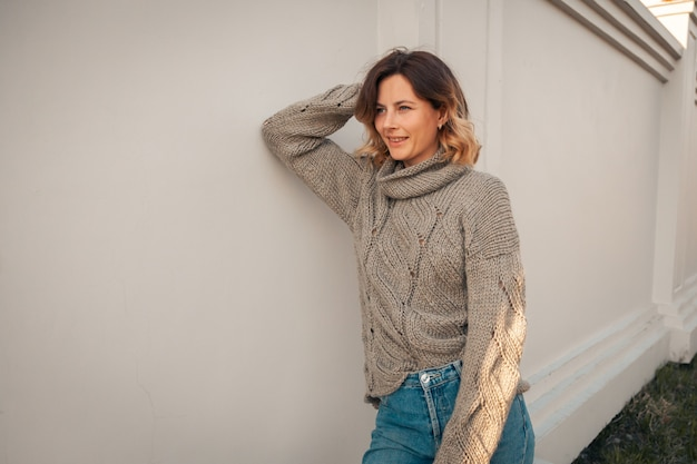 Belle jeune femme en pull en tricot marron en automne parc. concept de marche d'automne.