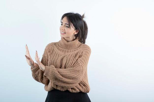 Belle jeune femme en pull tricoté montrant quelque chose sur un mur blanc