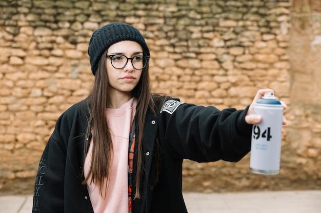 Belle jeune femme pulvérisation d'aérosol peut se tenir devant le mur de pierre