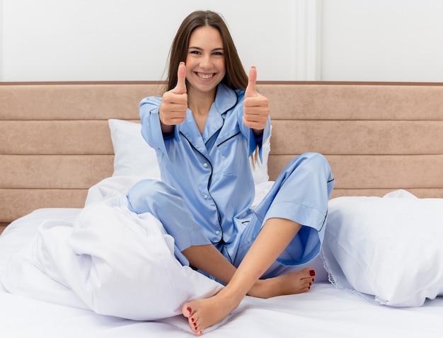 Belle jeune femme en pyjama bleu assis sur le lit au repos montrant les pouces vers le haut souriant heureux et positif profitant du week-end à l'intérieur de la chambre