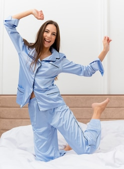 Belle jeune femme en pyjama bleu assis sur le lit au repos souriant heureux et positif profitant du week-end à l'intérieur de la chambre