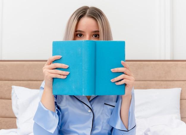 Belle jeune femme en pyjama bleu assis sur le lit avec un livre se cachant le visage furtivement dans l'intérieur de la chambre sur fond clair
