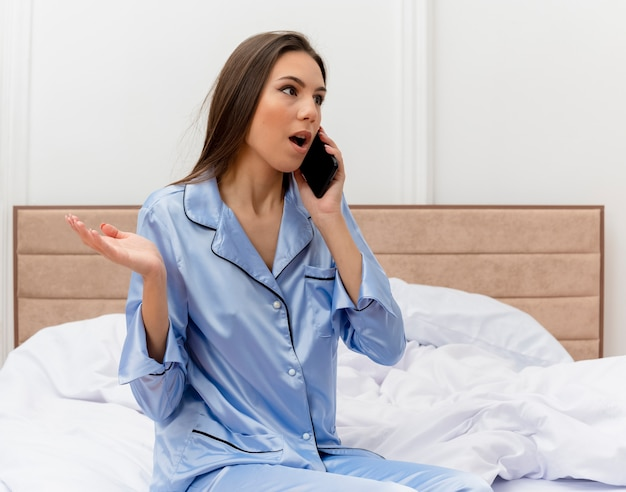Belle jeune femme en pyjama bleu assis sur le lit, parler au téléphone mobile à la confusion dans l'intérieur de la chambre sur fond clair