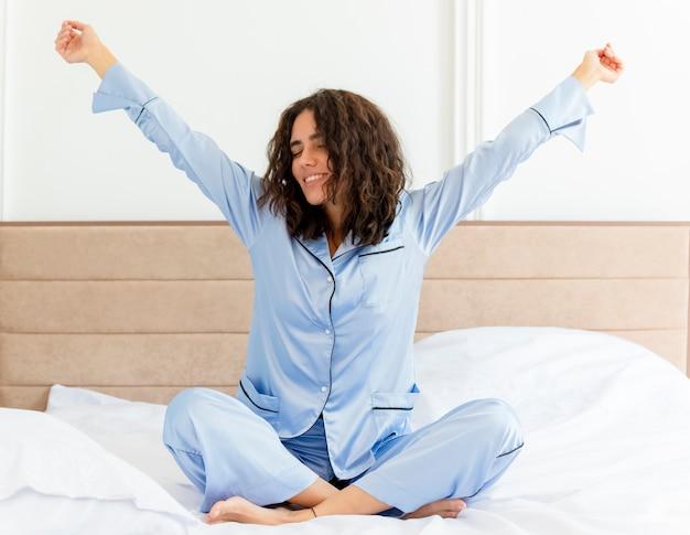 Belle jeune femme en pyjama bleu assis sur le lit se serrant les mains se réveiller heureux et positif en profitant de l'heure du matin dans l'intérieur de la chambre sur fond clair