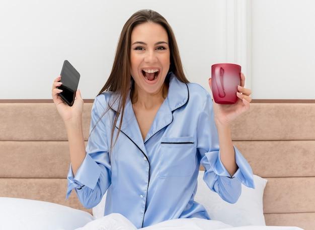 Belle jeune femme en pyjama bleu assis sur le lit avec une tasse de café tenant le smartphone regardant la caméra heureux et excité à l'intérieur de la chambre sur fond clair
