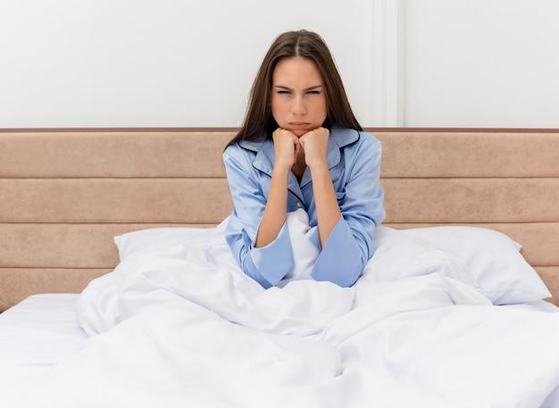 Belle jeune femme en pyjama bleu assis sur le lit avec un visage sérieux fronçant les sourcils mécontent à l'intérieur de la chambre